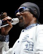 Snoop Dogg wearing blue Serious Pimp OG Bandana sunglasses during a concert