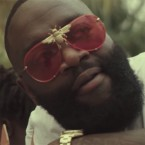 Rick Ross wears Tnemnroda I'll Be Rich Forever sunglasses in the music video for Monkey Suit.