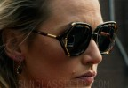 In the movie Triple 9, actress Kate Winslet wears a pair of tortoise and gold sunglasses with oversized, open temple frame design.