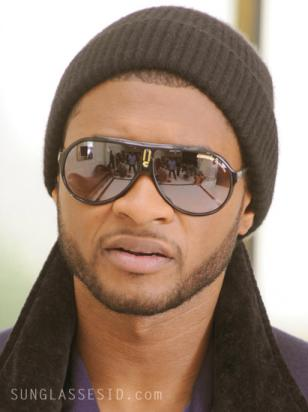 Usher is wearing a pair of black and gold Carrera Endurance sunglasses in the mu