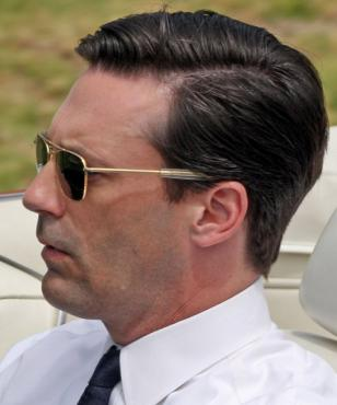 Jon Hamm, in a red convertible, wearing the RE Aviators during the filming of an