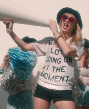 "Taylor Swift wears red heart-shaped sunglasses and a ""Not A Lot Going On At The Moment"" top in the 22 music video."