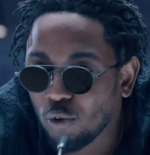 Kendrick Lamar wears a pair of round, grey Thom Browne sunglasses in the music video Bad Blood.